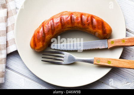 grilled sausage on plate with cutlery - Stock Photo