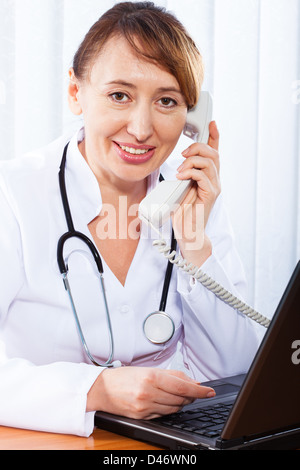Portrait of happy woman doctor in clinic. Woman doctor consults by phone - Stock Photo