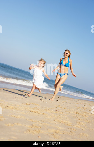 Mother And Daughter Running Along Beach - Stock Photo