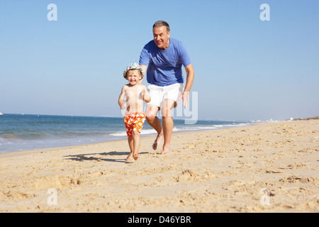 Grandfather And Grandson Running Along Beach - Stock Photo