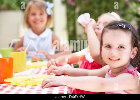 Group Of Children Enjoying Outdoor Tea Party - Stock Photo
