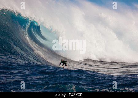 A tow-in surfer drops down the face of Hawaii's big surf at Peahi (Jaws) off Maui, Hawaii, USA. - Stock Photo