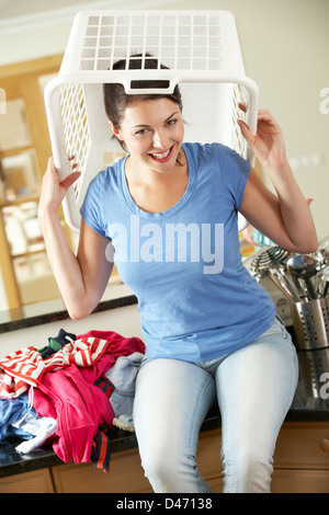 Woman Sitting On Kitchen Counter With Laundry Basket On Head - Stock Photo