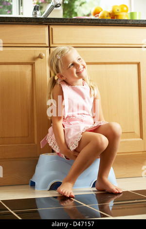 Girl Sitting On Plastic Step In Kitchen - Stock Photo