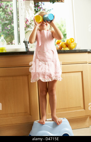 Girl Standing On Plastic Step In Kitchen Helping With Washing Up - Stock Photo