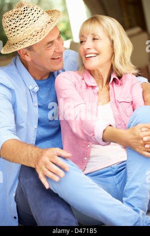 Senior Couple Sitting Outside House - Stock Photo