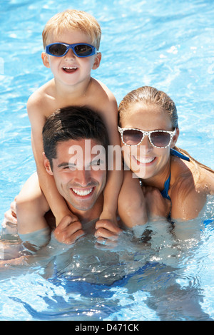 Family Having Fun In Swimming Pool - Stock Photo