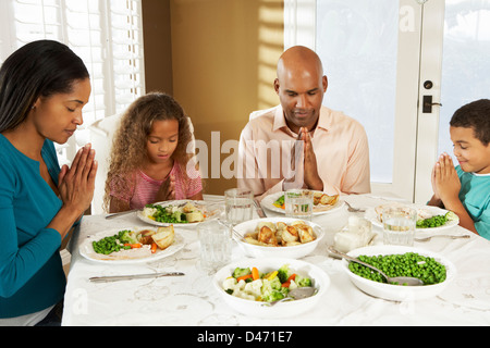 Family Saying Grace Before Meal At Home - Stock Photo