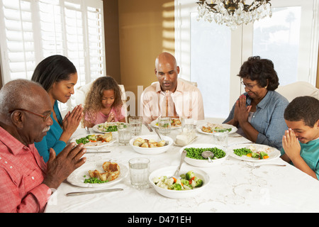 Multi Generation Family Saying Grace Before Meal At Home - Stock Photo