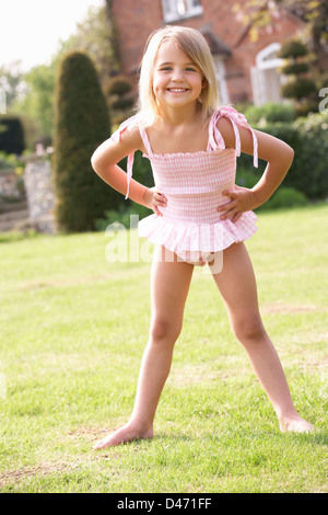 Portrait Of Young Girl Standing In Garden Wearing Swimming Costume - Stock Photo