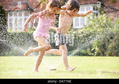 Two Children Running Through Garden Sprinkler - Stock Photo