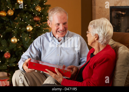 Senior Couple Exchanging Gifts In Front Of Christmas Tree - Stock Photo