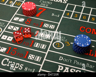 Casino chips and dice on a craps table. - Stock Photo