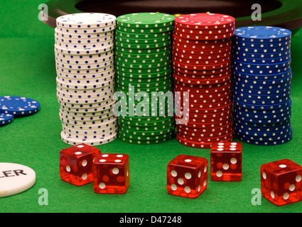 Stacked chips and dice on a green velvet background. - Stock Photo