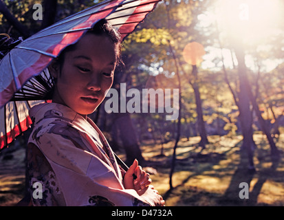Japan. Outdoor closeup of beautiful young Japanese woman wearing kimono and holding a parasol. - Stock Photo