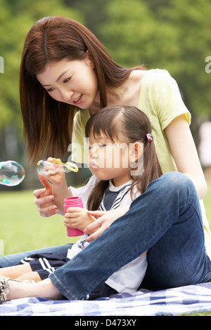 Chinese Mother With Daughter In Park Blowing Bubbles - Stock Photo