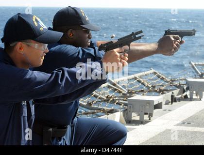 USS Lake Champlain Sailor work on gun qualifications. - Stock Photo