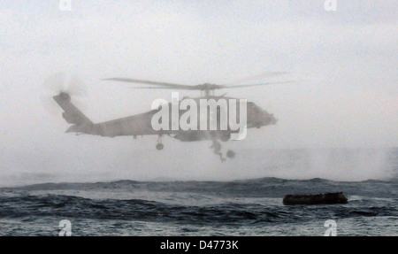 A SEAL jumps out of an HH-60H Sea Hawk helicopter during maritime operation training - Stock Photo