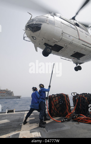 Sailors hook cargo net to an SA-330J Puma helicopter aboard USS Mitscher - Stock Photo
