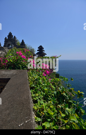 Bright bougainvillea with the meru of Pura Luhur Uluwatu in the background; Uluwatu; Bali, Indonesia. - Stock Photo