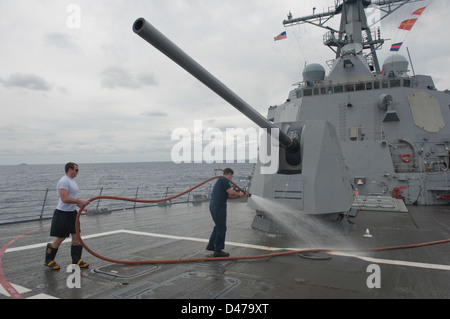 Sailors conduct a fresh water wash-down to clean the ship. - Stock Photo