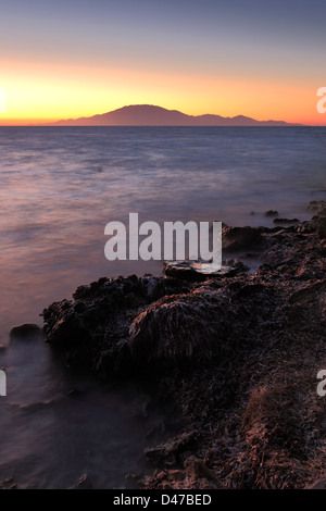 Sunset over the sweeping beach at Tsilivi town, with Kefalonia Island in the background, Greece, Europe. - Stock Photo