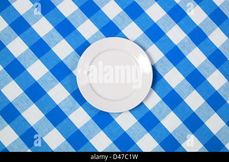 white round plate on blue checked tablecloth - Stock Photo
