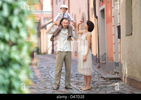 Happy young family in city street on beautiful summer day - Stock Photo