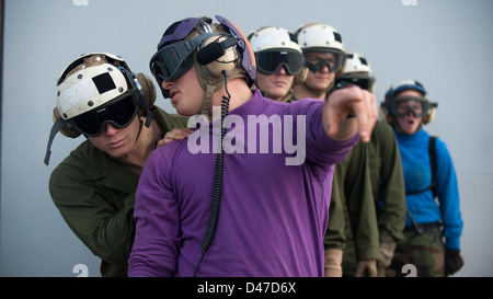 A Sailor directs a Marine on the flight deck. - Stock Photo