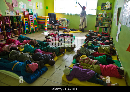 Children Sleeping On Floor Mats At A Daycare Center Stock