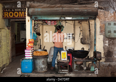 A Punjabi man selling sweets from a traditional food shop in the streets of Amritsar in the Indian state of Punjab. - Stock Photo