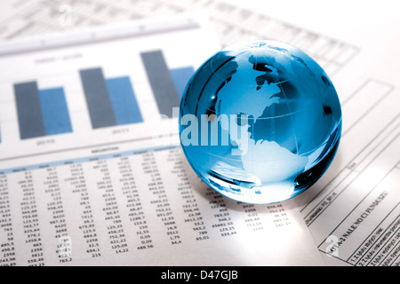 Globe showing North America and resting on financial papers - Stock Photo