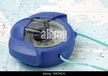 A marine hand-bearing compass on an old nautical chart - (chart is copyright free) - Stock Photo