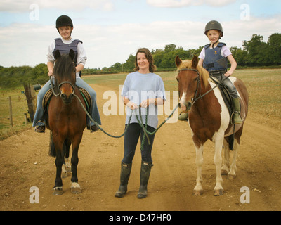 three females, a woman, mother leading  and two daughters on horse back - Stock Photo