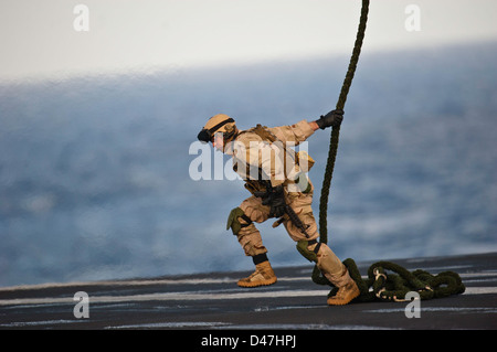 An explosive ordnance disposal technician demonstrates fast roping. - Stock Photo