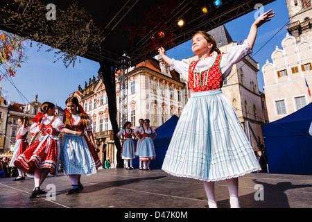 Dancing girls in traditional dress performing at the Easter Market stage in Old Town Square. Prague, Czech Republic - Stock Photo