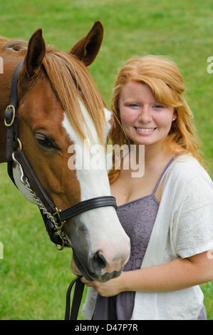 Smiling girl with her horse in portrait, head shot of a red haired teenager and her animal. - Stock Photo
