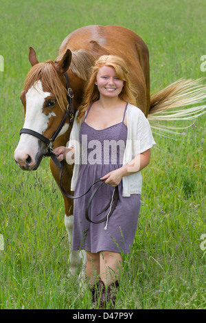 Young woman leading horse through grassy field, an eighteen year old red haired horsewoman. - Stock Photo