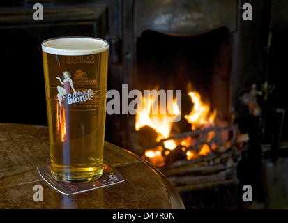 A pint of Dizzy Blonde beer on a pub table, with open fire in the background - Stock Photo