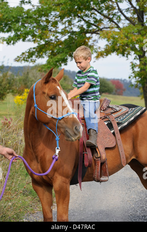 Young boy horseback riding on an adult saddle, a farm kid six years old enjoying himself smiling and happy aboard - Stock Photo