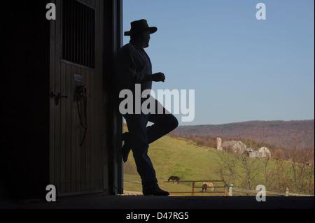 Open Barn Door farmer silhouette in open barn door with farm scenery in