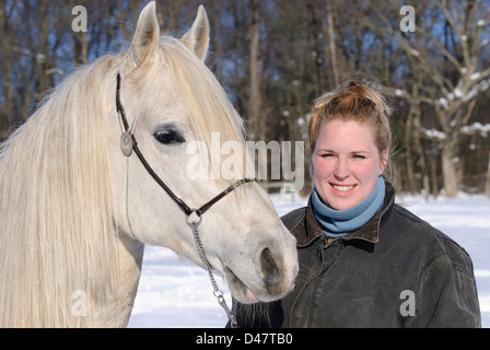 Woman and her white horse in outdoor winter snow portrait, a twenty-something blond and an Arabian stallion. - Stock Photo