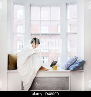Japanese young man using laptop while sitting on window sill and drinking coffee on a cold day in London - Stock Photo