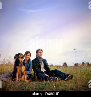 A boy, a girl, and a dog, open field, late afternoon, hanging out. MF film scan. - Stock Photo