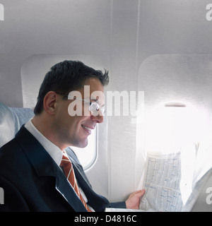 A businessman reading the financial section of a newspaper while travelling in an airplane. - Stock Photo