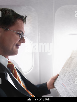 A businessman reading the business and finance section of a newspaper, in a plane. - Stock Photo