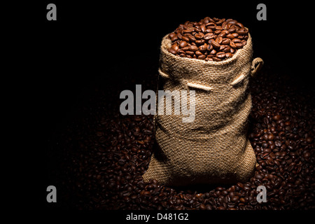 bag filled with coffee beans in spotlight - Stock Photo