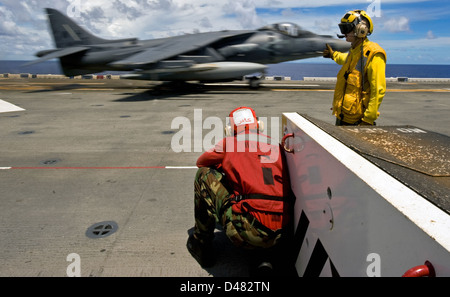 A Sailor directs the launch of an Harrier jet. - Stock Photo