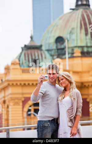 Young couple sightseeing in city, taking a picture. Federation Square, Melbourne, Victoria, Australia - Stock Photo