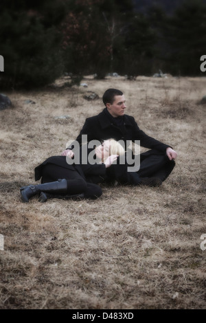a couple in black clothes is lying on a meadow in winter